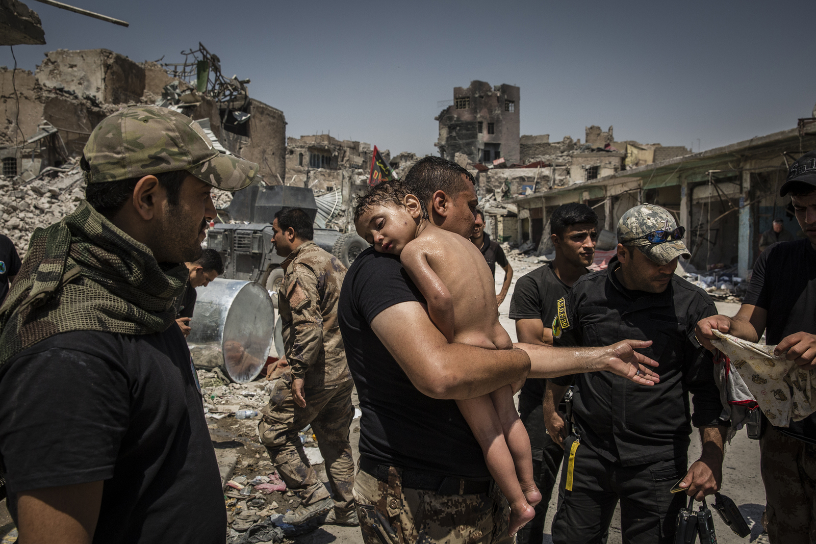 An unidentified young boy who was carried out of the last ISIS controlled area in the Old City by a man suspected of being a militant is cared for by Iraqi Special Forces soldiers. The soldiers suspected the man had used the boy as a human shield in order to try and escape as he did not know the child's name and claimed he had just found him alone in the street. One of the soldiers agreed to adopt the boy given that they knew nothing about him and he didn't speak. 12/07/2017